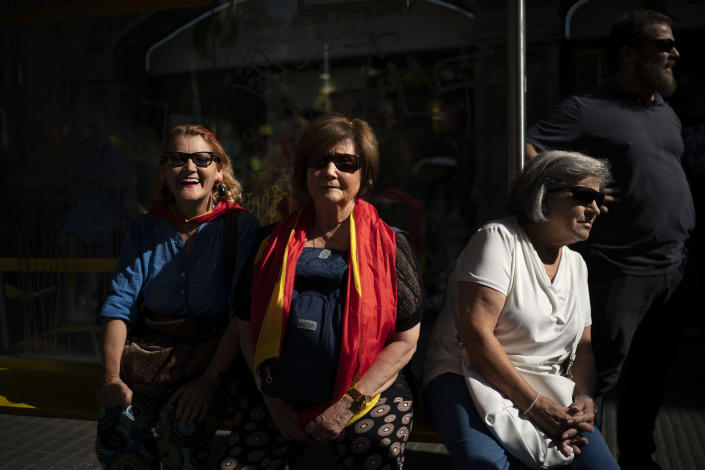 Supporters wearing Spanish flags watch as members of National Police and Guardia Civil march during a protest demanding better pay in Barcelona, Spain, Saturday, Sept. 29, 2018. (AP Photo/Felipe Dana)