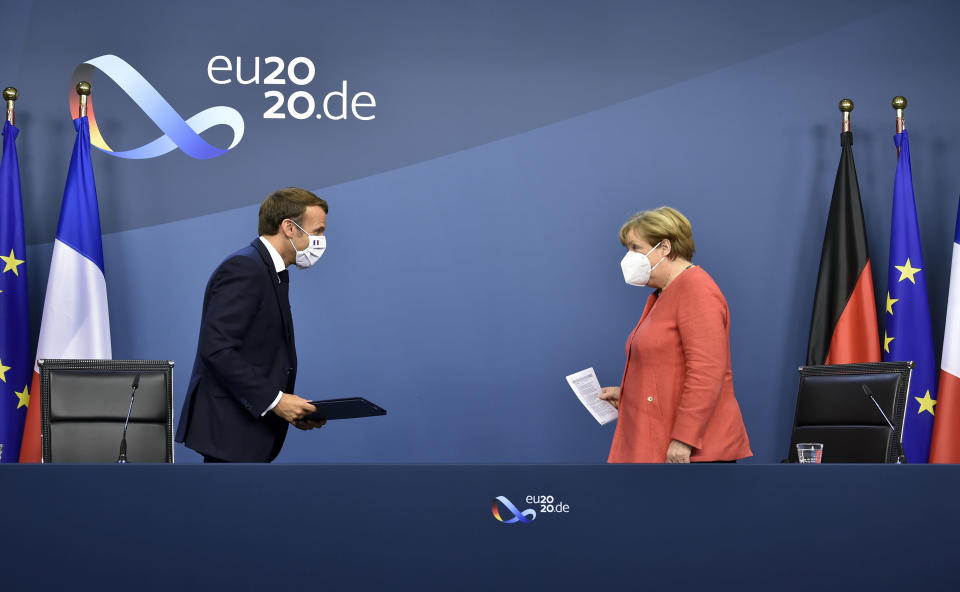 FILE - In this Tuesday, July 21, 2020 file photo, German Chancellor Angela Merkel, right, and French President Emmanuel Macron prepare to address a media conference at the end of an EU summit in Brussels, after finally clinched an unprecedented budget and coronavirus recovery fund. A last-minute trade deal with the United Kingdom coupled with the rollout of COVID-19 vaccines in the final days of the year produced a sense of success for the 27-nation bloc and brought glimmers of hope to the EU's 450 million residents. (John Thys/Pool Photo via AP, File)