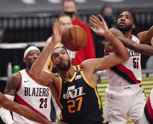 Portland Trail Blazers forward Derrick Jones Jr., right, and Utah Jazz center Rudy Gobert, middle, vie for a rebound as Trail Blazers forward Robert Covington, left, watches during the first half of an NBA basketball game in Portland, Ore., Wednesday, Dec. 23, 2020. (AP Photo/Steve Dipaola)