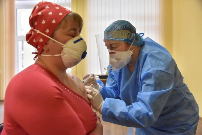 A medical worker receives a dose of the AstraZeneca vaccine against the coronavirus disease in Lviv