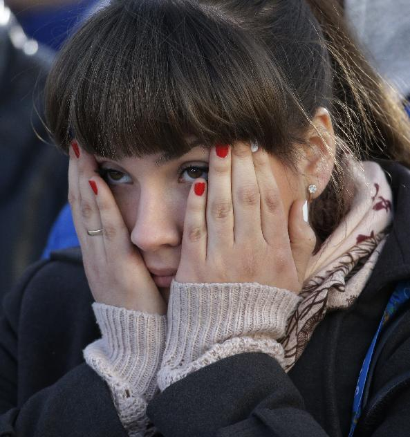 A fan covers her face while watching the men's ice hockey game between Russia and Finland on a large screen in Olympic Park, at the 2014 Winter Olympics, Wednesday, Feb. 19, 2014, in Sochi, Russia