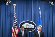 Assistant Attorney General for National Security John Demers, left, and FBI Director Christopher Wray participate in a virtual news conference at the Department of Justice, Wednesday, Oct. 28, 2020 in Washington. The Justice Department has charged eight people with working on behalf of the Chinese government to locate Chinese dissidents and political opponents living in the U.S. and coerce them into returning to China. Five of the eight were arrested Wednesday morning. (Sarah Silbiger/Pool via AP)