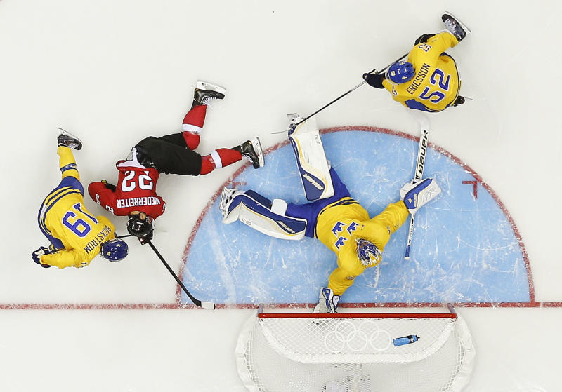 Sweden goaltender Henrik Lundqvist blocks a shot on goal by Switzerland in the first period of a men's ice hockey game at the 2014 Winter Olympics, Friday, Feb. 14, 2014, in Sochi, Russia. (AP Photo/Julio Cortez )