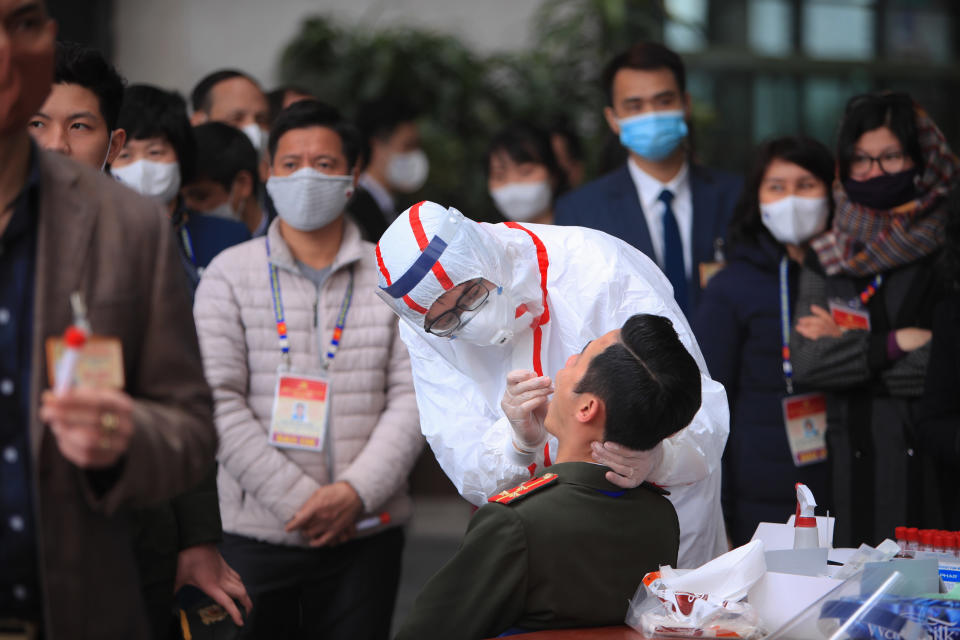 """FILE - In this Friday, Jan. 29, 2021 file photo, a health worker takes swab samples of a security officer to test for COVID-19 at the venue of Vietnam Communist Party congress in Hanoi, Vietnam. On Friday, The Associated Press reported on stories circulating online incorrectly asserting the World Health Organization admits that PCR tests to diagnose COVID-19 gave massive false positives, overinflating COVID-19 case numbers. WHO told The Associated Press that it has received 10 reports of problems related to PCR tests for the detection of SARS-CoV-2. """"The reports were for misdiagnosis, both false positive and false negative results,"""" according to WHO. (AP Photo/Hau Dinh)"""