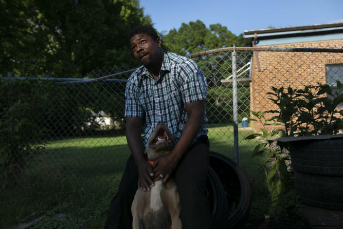 La Jarvis D. Love strokes one of several dogs he keeps at his home in Senatobia, Miss., Sunday, June 9, 2019. Love says the dogs protect his wife and three children. (AP Photo/Wong Maye-E)