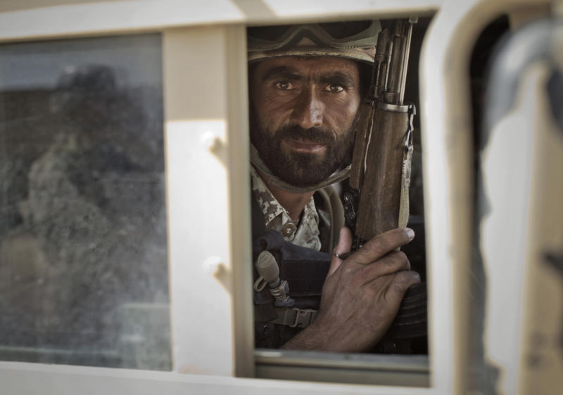 In this Friday, Oct. 19, 2012 photo, a member of Afghanistan's elite Civil Order Police looks through a window of his armored vehicle during a patrol in Marjah, southern Helmand province, Afghanistan. As the U.S. and NATO close out their mission in Afghanistan preparing for the final withdrawal of combat troops by the end of 2014, the worry looms large that fresh outbursts of ethnically motivated fighting would send the country into a spiral of chaos and violence. (AP Photo/Anja Niedringhaus)