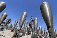 A member of the Iraqi security forces stands between Islamic State ammunition being displayed in al-Alam Salahuddin province, Iraq in this March 17, 2015 file photo. REUTERS/Thaier Al-Sudani/Files