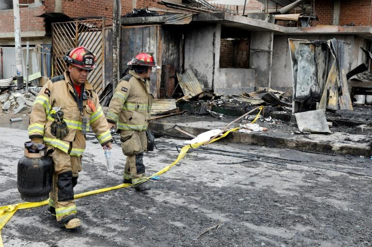 Firefighters walk past destroyed houses after the explosion of a gas tanker in Lima left at least eight people dead and dozens injured