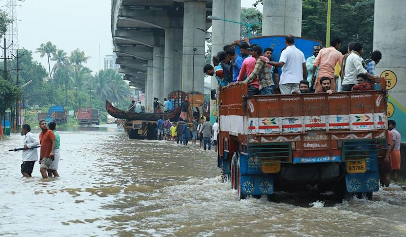 Commuters travel on a truck in the Ernakulam district of Kochi.