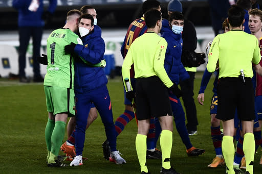 Barcelona's goalkeeper Marc-Andre ter Stegen, left, is greeted by teammate Lionel Messi at the end of the Spanish Super Cup semi final soccer match between Barcelona and Real Sociedad at Nuevo Arcangel stadium in Cordoba, Spain, Wednesday, Jan. 13, 2021. Barcelona will play the final after defeating Real Sociedad 3-2 in a penalty shootout after the game ended 1-1. (AP Photo/Francisco Seco)