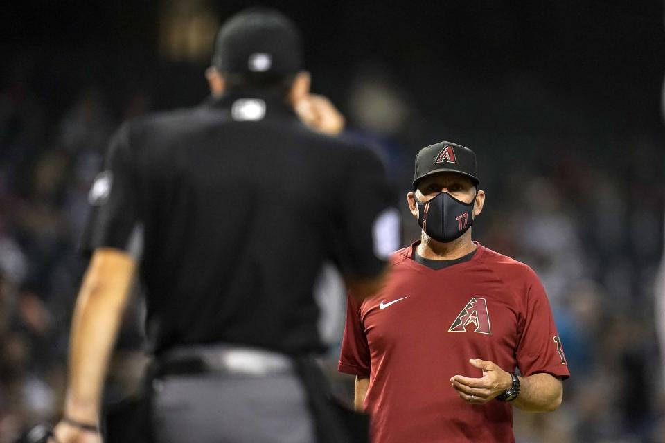 Arizona Diamondbacks manager Torey Lovullo, right, argues with umpire David Rackley during the third inning of a baseball game against the Oakland Athletics Monday, April 12, 2021, in Phoenix. (AP Photo/Ross D. Franklin)