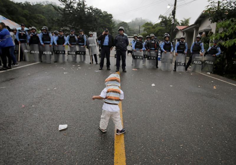 A young migrant child is confronted by police.