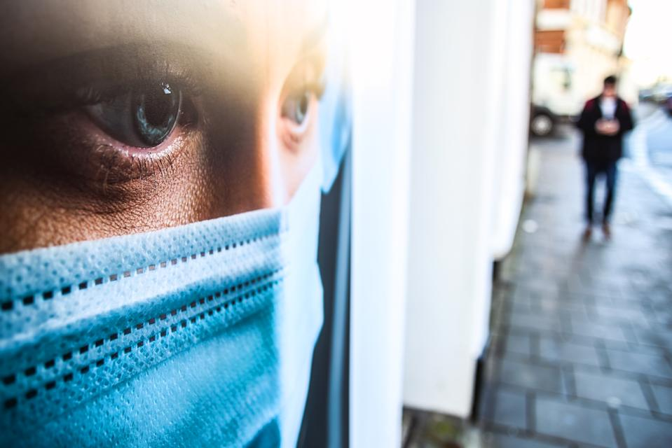A man walks past a window display that shows an NHS worker wearing a protective face mask in Worthing, Sussex, as the UK continues in a third lockdown due to the coronavirus pandemic. Picture date: Tuesday February 23, 2021.