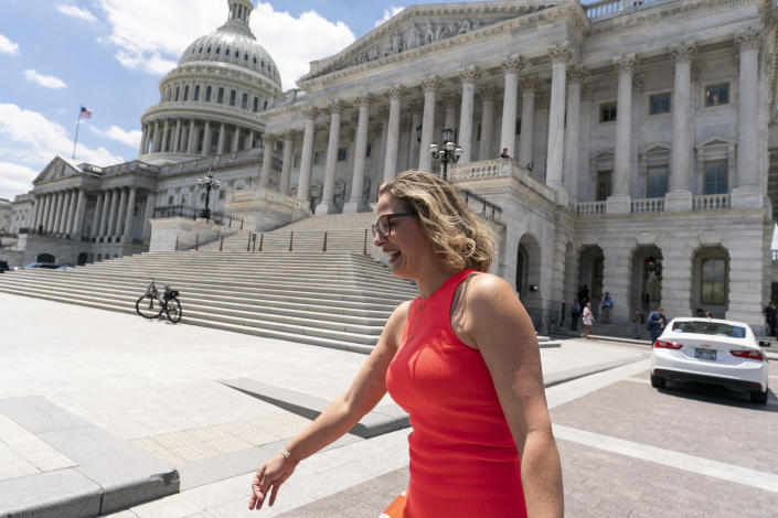 FILE - In this June 24, 2021, file photo, Sen. Kyrsten Sinema, D-Ariz., smiles as she returns to the Capitol after a meeting with President Joe Biden at the White House in Washington. More than her shock of purple hair or unpredictable votes Sinema is perhaps best known for doing the unthinkable in Washington: spending time on the Republican side of the aisle. Her years in Congress have been a whirlwind of political style and perplexing substance, an anti-war liberal-turned-deal-making centrist who now finds herself at the highest levels of power.(AP Photo/Alex Brandon)