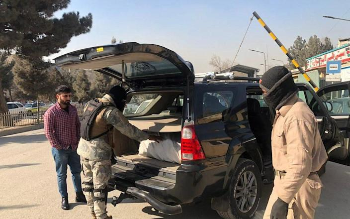 Afghan security officials check vehicles at a checkpoint in Kabul, Afghanistan - Shutterstock/Shutterstock