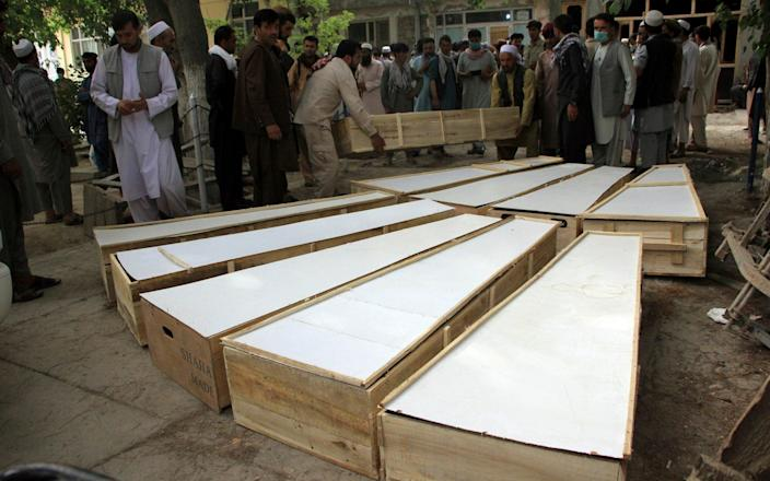 The coffins of the victims in Tuesday's attack are placed on the ground at a hospital in northern Baghlan province, Afghanistan, Wednesday, June 9, 2021. Workers of the HALO Trust de-mining organization were attacked on Tuesday night by the armed gunmen. (AP Photo/Mehrab Ibrahimi) - AP