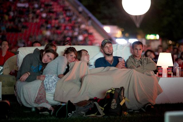 German soccer fans watch the opening game of the soccer World Cup 2014, while sitting on sofas in the 1.FC Union stadium in Berlin, Thursday, June 12, 2014. (AP Photo/Axel Schmidt)