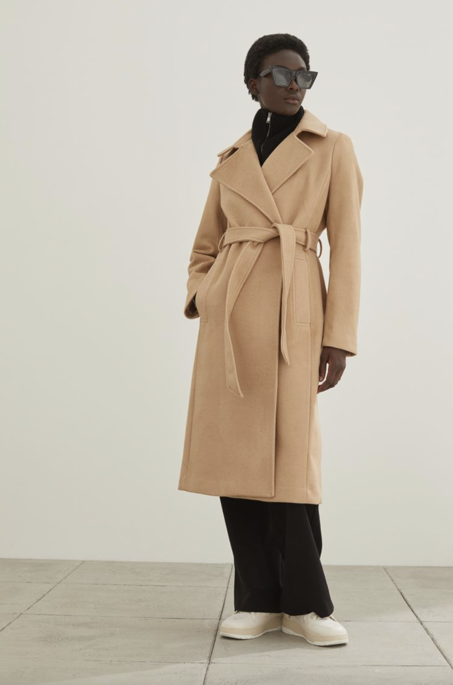 black model with short hair wearing camel Tie Belt Coat, black pants, and white shoes