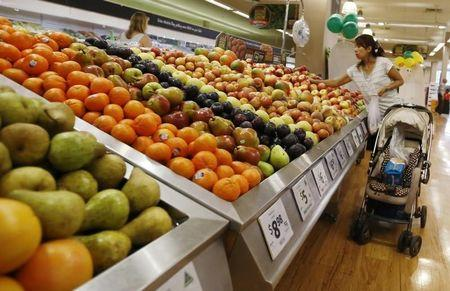 A women selects apples at a supermarket in Sydney