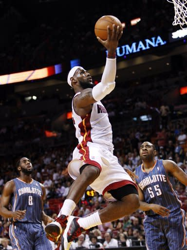 Miami Heat forward LeBron James shoots as Charlotte Bobcats forwards D.J. White (8) and Reggie Williams (55) watch during the first half of an NBA basketball game, Friday, April 13, 2012, in Miami. (AP Photo/Wilfredo Lee)