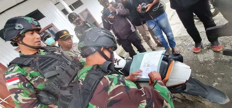 Indonesian security forces sign release forms for family members collecting the bodies of the Bagau brothers at the Sugapa health clinic in Intan Jaya regency, Papua