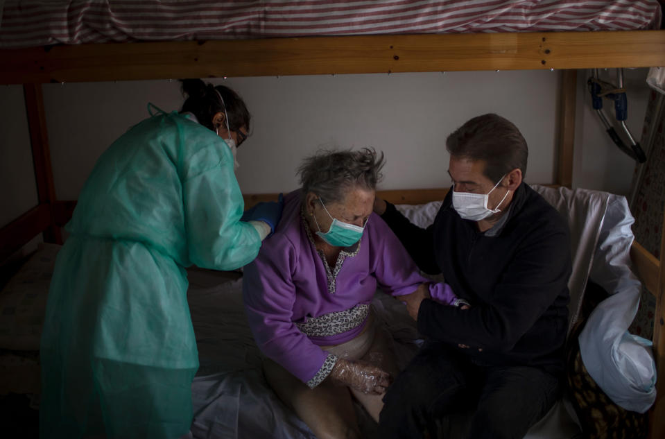 A home care doctor performs a physical exam on Felicidad while her son, Joan, holds her arm at her home in Barcelona, Spain, March 31, 2020. Felicidad had been admitted to the hospital after suffering a stroke but was sent home within a day and soon developed respiratory symptoms. (AP Photo/Emilio Morenatti)