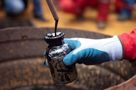 FILE PHOTO: A worker collects a crude oil sample at an oil well operated by Venezuela's state oil company PDVSA in Morichal, Venezuela, July 28, 2011.   REUTERS/Carlos Garcia Rawlins/File Photo