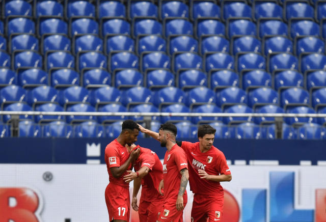Augsburg's Noah Saranren Bazee, left, celebrates with teammates after scoring his side's second goal during the German Bundesliga soccer match between FC Schalke 04 and FC Augsburg at the Veltins-Arena in Gelsenkirchen, Germany, Sunday, May 24, 2020. The German Bundesliga becomes the world's first major soccer league to resume after a two-month suspension because of the coronavirus pandemic. (AP Photo/Martin Meissner, Pool)