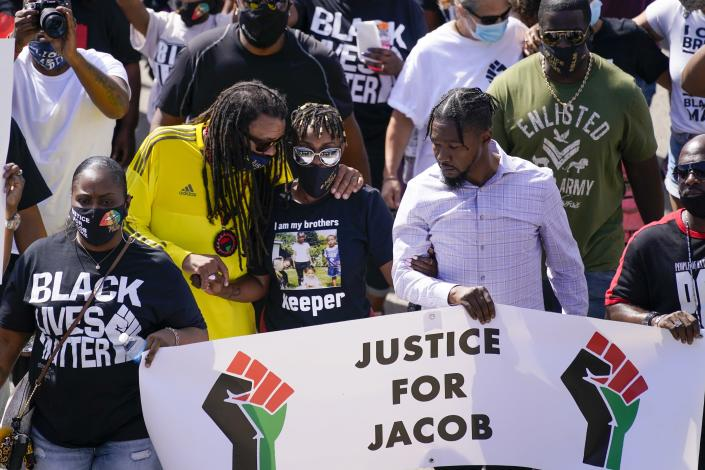 Jacob Blake's sister Letetra Widman, center, and uncle Justin Blake, left, march at a rally for Jacob Blake Saturday, Aug. 29, 2020, in Kenosha, Wis. (AP Photo/Morry Gash)