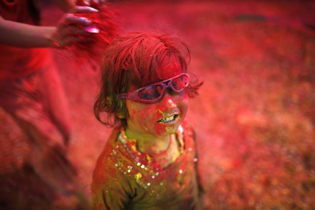 A girl daubed in colours takes part in the Holi celebrations organised by non-governmental organisation Sulabh International at a widows' ashram in Vrindavan in the northern Indian state of Uttar Pradesh March 14, 2014. Traditionally in Hindu culture, widows are expected to renounce earthly pleasure so they do not celebrate Holi. But women at the shelter for widows, who have been abandoned by their families, celebrated the festival by throwing flowers and coloured powder. Holi, also known as the Festival of Colours, heralds the beginning of spring and is celebrated all over India. REUTERS/Ahmad Masood (INDIA - Tags: ANNIVERSARY RELIGION SOCIETY)