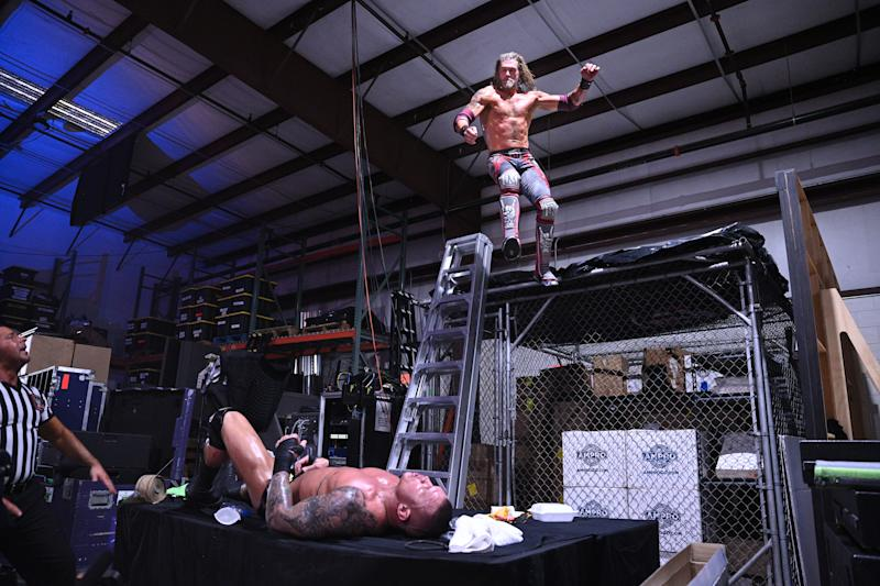 Edge uses an elbow drop to put Randy Orton through a table. (Photo Credit: WWE)