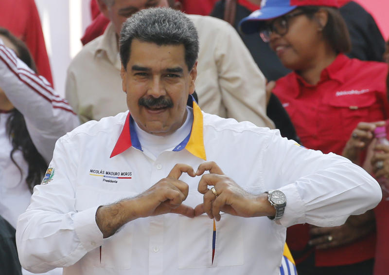 "In this May 20, 2109 photo, Venezuela's President Nicolas Maduro flashes a hand-heart symbol to supporters outside Miraflores presidential palace in Caracas, Venezuela. Maduro said Thursday, May 23, 2019, that he iss inviting China's Huawei to help set up a 4G network in Venezuela, prompting opposition leader Juan Guaidó to accuse him of having an ""absolute disconnection with reality."" (AP Photo/Ariana Cubillos)"