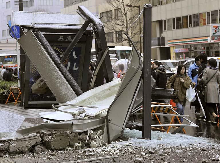 People walk past a ruined bus stop which was crushed by part of fallen outer wall of a nearby building in Sendai, Miyagi Prefecture (state) after Japan was struck by a strong earthquake off its northeastern coast Friday, March 11, 2011. (AP Photo/Kyodo News)