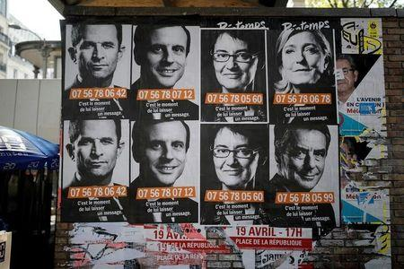 "A poster campaign with factice portable cellphone numbers for French presidential candidates, Top row from L, Benoit Hamon, Socialist Party candidate, Emmanuel Macron, candidate for ""En Marche !"" or (Onwards !),  Nathalie Arthaud, candidate for France's extreme-left Lutte Ouvriere, and Marine Le Pen, the National Front (FN) leader and candidate; Bottom row R, Francois Fillon, the Republicans centre-right candidate, are seen on a wall in Paris, France, April 19, 2017.   REUTERS/Benoit Tessier"