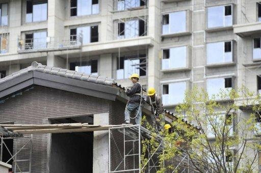 Workers stand on scaffoldings at a construction site in Beijing, April 12, 2012. China's growth slowed to 9.2 percent last year from 10.4 percent in 2010, dragged down by the global slowdown and domestic tightening aimed at controlling inflation