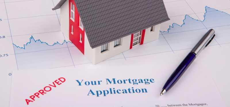 A mortgage application next to model home and line graph