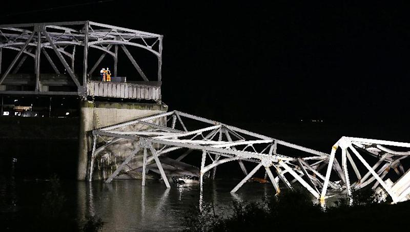 Officials look on from the remaining structure at the collapsed Interstate-5 bridge submerged below in the Skagit River in Mount Vernon, Wash., Thursday, May 23, 2013. At least two vehicles went into the river. (AP Photo/Elaine Thompson)