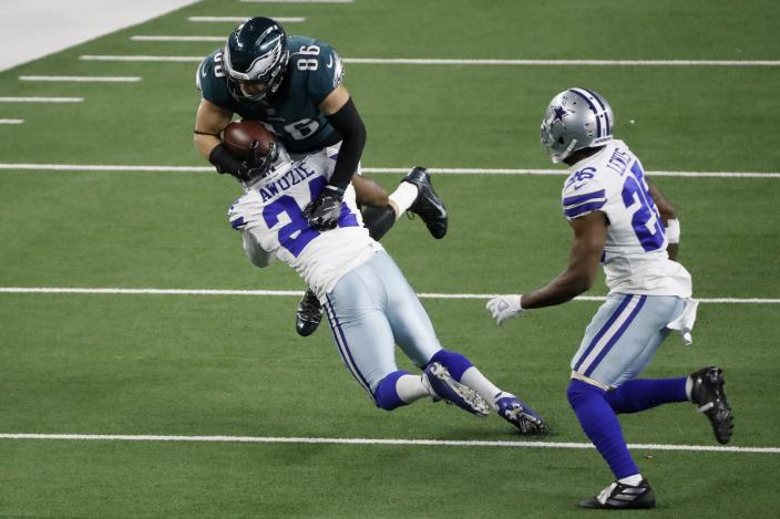 Dallas Cowboys cornerback Chidobe Awuzie (24) stops Philadelphia Eagles tight end Zach Ertz (86) from gaining extra yardage after a catch as cornerback Jourdan Lewis (26) looks on in the second half of an NFL football game in Arlington, Texas, Sunday, Dec. 27. 2020. (AP Photo/Roger Steinman)
