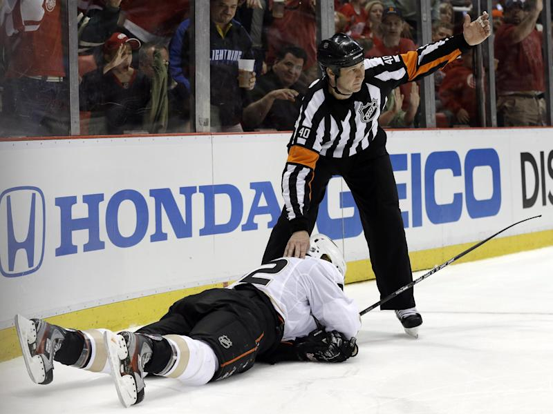 Referee Steve Kozari signals to the bench for a trainer after Anaheim Ducks defenseman Toni Lydman, of Finland, was checked by Detroit Red Wings' Justin Abdelkader during the second period in Game 3 of a first-round NHL hockey Stanley Cup playoff series in Detroit, Saturday, May 4, 2013. (AP Photo/Paul Sancya)