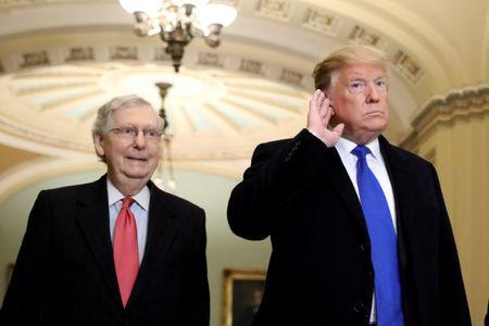 FILE PHOTO: U.S. President Donald Trump listens to a question from reporters next to Senate Majority Leader Mitch McConnell (R-KY) as he arrives for a closed Senate Republican policy lunch on Capitol Hill in Washington, U.S., March 26, 2019. REUTERS/Brendan McDermid/File Photo