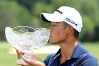 Collin Morikawa celebrates with the winner's trophy after the final round of the Workday Charity Open