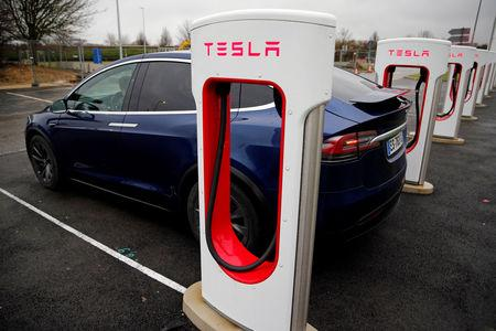 FILE PHOTO: A driver recharges the battery of his Tesla car at a Tesla Super Charging station in a petrol station on the highway in Sailly-Flibeaucourt