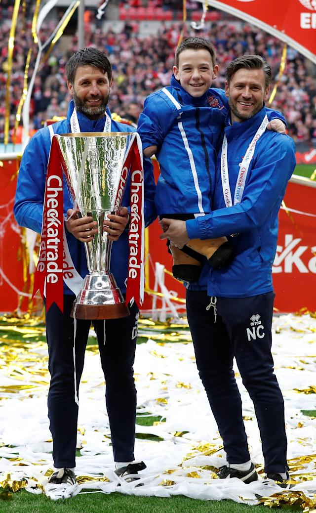 "Soccer Football - Checkatrade Trophy Final - Lincoln City vs Shrewsbury Town - Wembley Stadium, London, Britain - April 8, 2018 Lincoln City manager Danny Cowley (L) with mascot and Nicky Cowley (R) celebrate with the trophy after winning the Checkatrade Trophy Final Action Images/Matthew Childs EDITORIAL USE ONLY. No use with unauthorized audio, video, data, fixture lists, club/league logos or ""live"" services. Online in-match use limited to 75 images, no video emulation. No use in betting, games or single club/league/player publications. Please contact your account representative for further details."