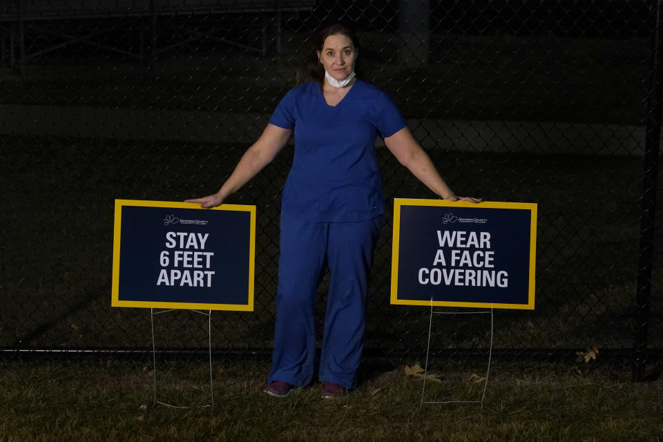 Emergency room nurse L'Erin Ogle poses with coronavirus signs after getting off a 12-hour shift at a nearby hospital where she works Monday, March 8, 2021, in Overland Park, Kan. After a year of working long hours taking care of COVID-19 patients, Ogle feels obligated to speak out when she sees misinformation related to the pandemic in her community. (AP Photo/Charlie Riedel)