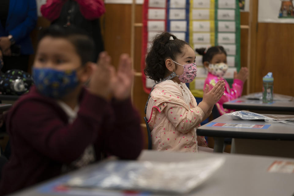 First graders applaud while listening to their teach in a classroom on the first day of in-person learning at Heliotrope Avenue Elementary School in Maywood, Calif., Tuesday, April 13, 2021. More than a year after the pandemic forced all of California's schools to close classroom doors, some of the state's largest school districts are slowly beginning to reopen this week for in-person instruction. (AP Photo/Jae C. Hong)