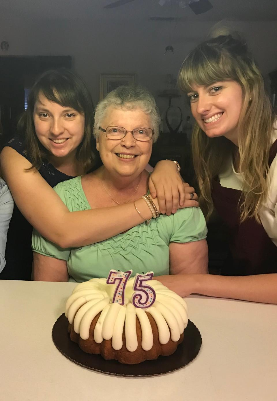 This June 3, 2018 photo shows Megan Hockman, from left, her grandmother Eleanor Raguse and sister Kayla Hockman posing with a birthday cake for Raguse in Fontana, Calif. The Hockmans plan a painting party with a remote brunch on Raguse's lawn as she paints and munches from her porch on Mother's Day. Isolation due to the coronavirus outbreak has led mothers and offspring to find creative ways to celebrate. (Lori Hockman via AP)