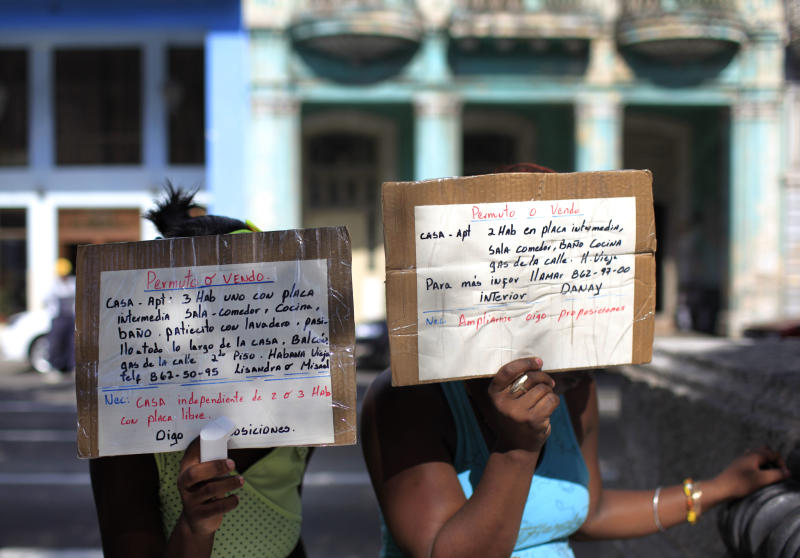 In this April 20, 2013 photo, women hold up homemade signs advertising homes for sale or rent, in Havana, Cuba. A baffling, sometimes bizarre real estate market has emerged in the year and a half since President Raul Castro legalized private home sales in Cuba, for the first time in five decades. While trade in homes is now legal, the people who bring buyers together with sellers are not. (AP Photo/Franklin Reyes)