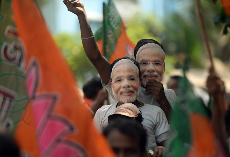 India's Bharatiya Janata Party supporters wear masks of then prime minister-designate Narendra Modi during a celebration rally in Mumbai on May 26, 2014 (AFP Photo/Punit Paranjpe)