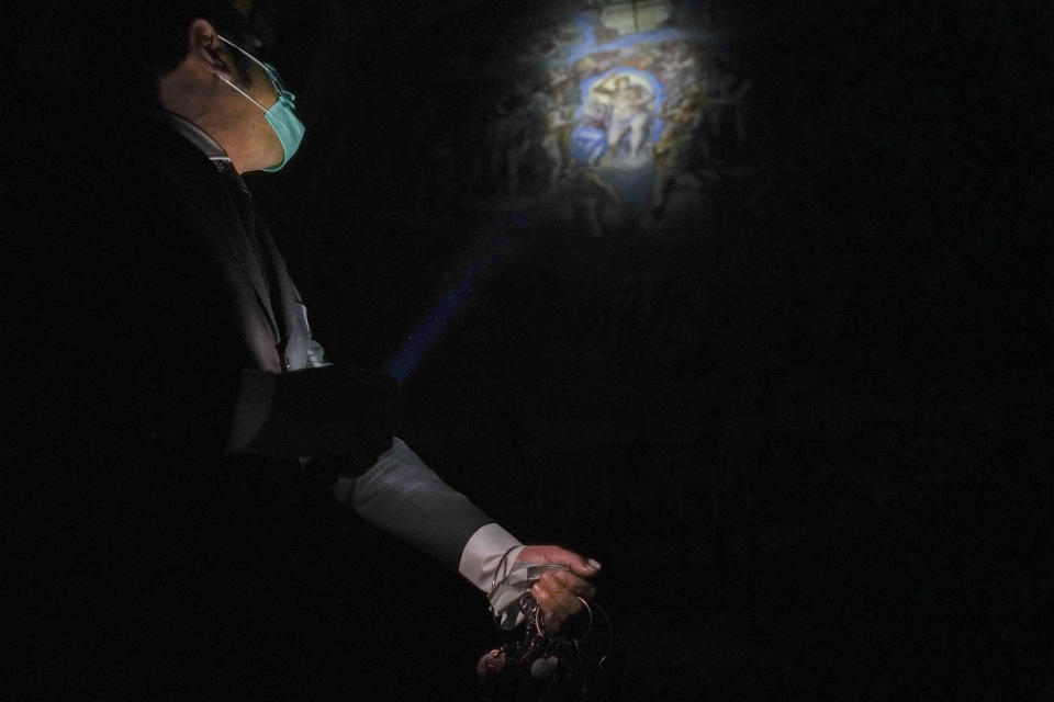 "Gianni Crea, the Vatican Museums chief ""Clavigero"" key-keeper, uses a torch to illuminate the Sistine Chapel prior to switching on the lights as he opens it, at the Vatican, Monday, Feb. 1, 2021. Crea is the ""clavigero"" of the Vatican Museums, the chief key-keeper whose job begins each morning at 5 a.m., opening the doors and turning on the lights through 7 kilometers of one of the world's greatest collections of art and antiquities. The Associated Press followed Crea on his rounds the first day the museum reopened to the public, joining him in the underground ""bunker"" where the 2,797 keys to the Vatican treasures are kept in wall safes overnight. (AP Photo/Andrew Medichini)"