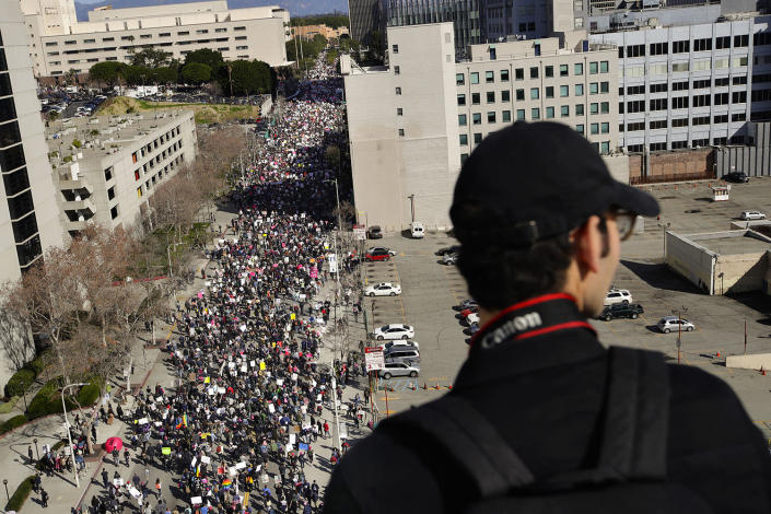 <p>Derek Avila stands on the rooftop of a building as thousands of protesters fill the streets of downtown Los Angeles to protest against President Donald Trump, Saturday, Jan. 21, 2017. (AP Photo/Jae C. Hong) </p>